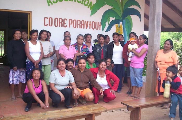 Un grupo de mujeres posa frente a una edificacion con el nombre de la asociacion Coore Poraviqui.